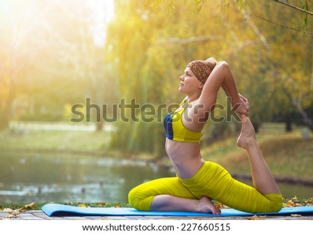 Young woman doing yoga in autumn park near lake - stock photo