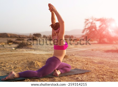 Young woman doing yoga in desert at sunrise time - stock photo
