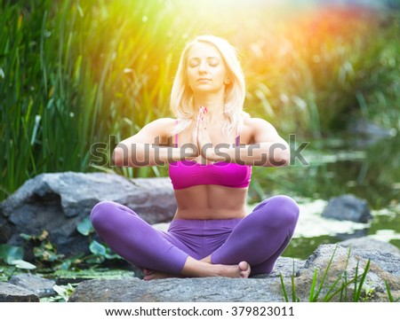 Young woman doing yoga in morning beautiful nature near river