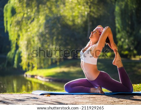 Young woman doing yoga in Park near lake - stock photo