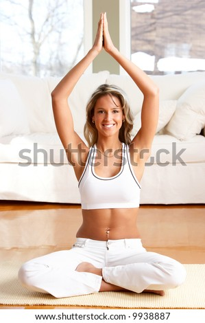 Young woman doing yoga in the sunny room - stock photo