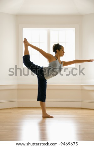 Young woman doing yoga king dancer pose indoors by sunlit window. - stock photo