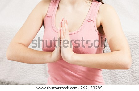 Young Woman Doing Yoga Meditating Relaxing Exercise in prayer position at home.Healthy Lifestyle.Unrecognizable caucasian female practicing meditation on the floor. - stock photo
