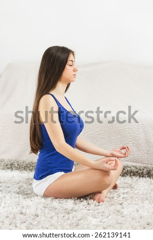 Young Woman Doing Yoga Meditation at home. Caucasian female relaxing .  Healthy Lifestyle. - stock photo