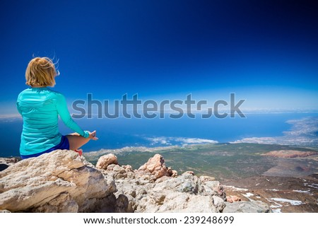 Young woman doing yoga meditation outside natural beautiful inspirational landscape environment, fitness and exercising motivation and inspiration in sunny mountains over blue sky and ocean sea. - stock photo
