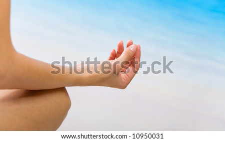 Young woman doing yoga moves or meditating on beach - stock photo