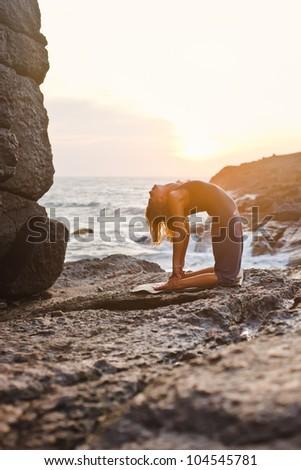 Young woman doing yoga on a rocky seashore. Doing camel pose (ushtrasana) - stock photo