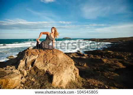 Young woman doing yoga on a rocky seashore. Doing pigeon pose - stock photo