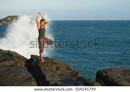 Young woman doing yoga on a rocky seashore. Doing tree pose (vrikshasana) - stock photo