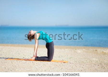 Young woman doing yoga on beach