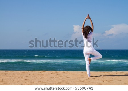 young woman doing yoga on beach - stock photo