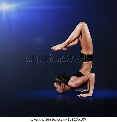 Young woman doing yoga on blue abstract background - stock photo