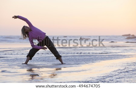 Young woman doing yoga on coast of sea on beach. Young woman silhouette practicing yoga on the sea beach at sunset.