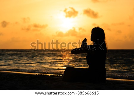 young woman doing yoga on sunset beach