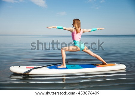 Young woman doing yoga on sup board with paddle. Meditative pose, side view - concept of harmony with the nature, free and healthy living, freelance, remote business. - stock photo