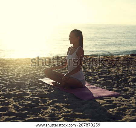 young woman doing yoga on the beach at sunrise.