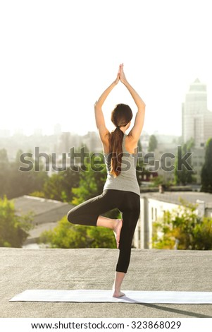 Young woman doing yoga on the mat on the roof  and looking at city - stock photo