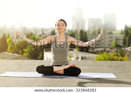 Young woman doing yoga on the mat on the roof, sitting in lotus posture and meditating - stock photo