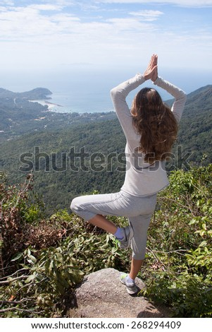 Young woman doing yoga on top of a mountain - stock photo