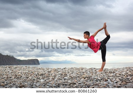 Young woman doing yoga stretch on stone beach at lake Baikal. - stock photo