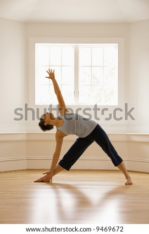 Young woman doing yoga triangle pose indoors by sunlit window. - stock photo