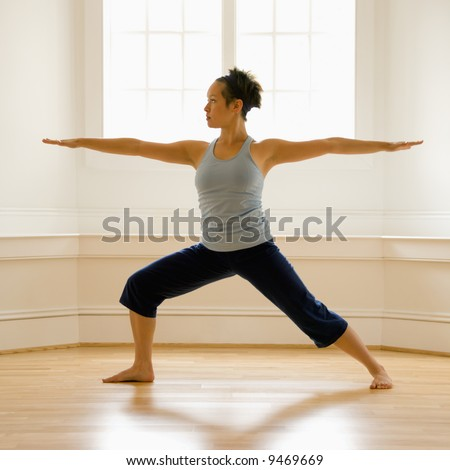 Young woman doing yoga warrior pose indoors by sunlit window. - stock photo