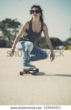 Young woman down the road with a skateboard - stock photo