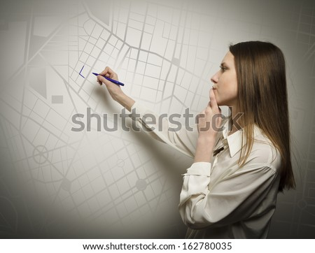 Young woman drawing a route on the city map - stock photo