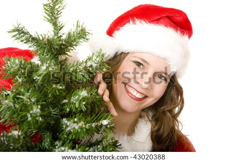 young woman dressed as Santa Claus is standing beside a Christmas tree and smiles happy. Isolated on white. - stock photo