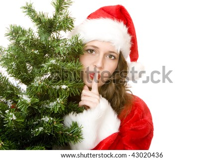 Young woman dressed as Santa Claus stands beside a Christmas fir tree and puts finger on lips to get silence. Isolated on white. - stock photo