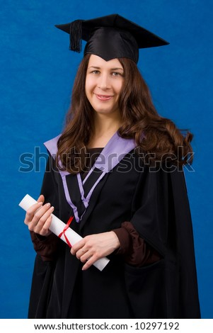 Young woman dressed in black graduation gown holding certificate of degree, standing over blue background.