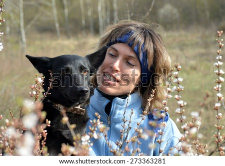Young woman dressed in blue clothes is nearly her favorite black dog. Situation in outdoor. Bloom tree is in the foreground. - stock photo