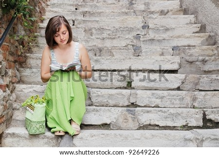 Young woman dressed in green sits on stairs and reads book - stock photo