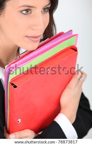 young woman dressed in suit holding file folders - stock photo