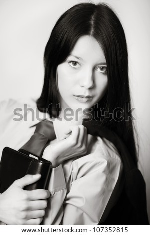 young woman dressed up in a man's shirt and tie holding a filofax - stock photo