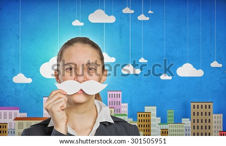 Young woman dressed up in suit and wearing fake mustache - stock photo