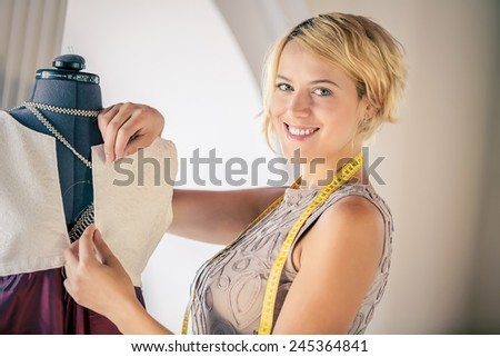 Young woman dressmaker at tailors making measures - stock photo