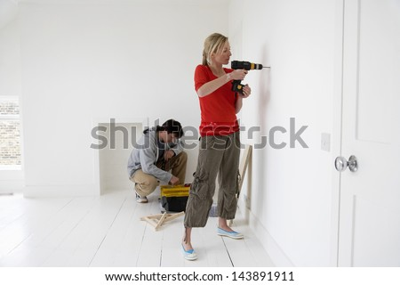Young woman drilling hole in the wall with man in background at their new home - stock photo