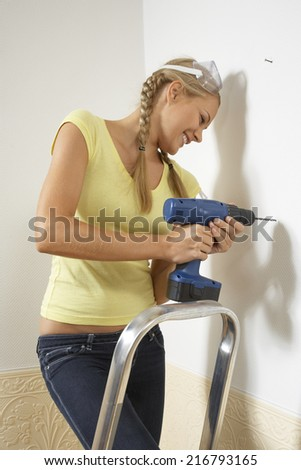 Young woman drilling into a wall - stock photo