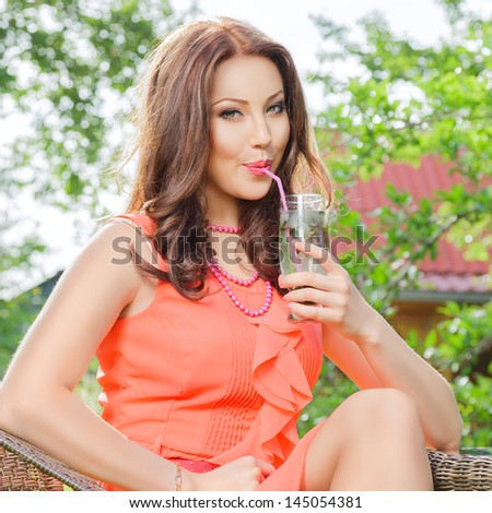Young woman drink cold mojito cocktail at outdoor cafe - stock photo