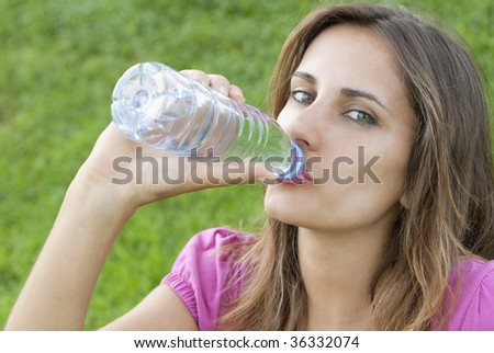 Young woman drink water sit grass portrait - stock photo