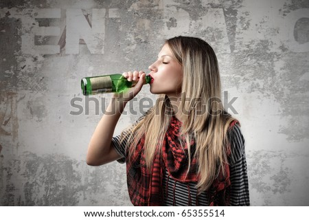 Young woman drinking a beer - stock photo