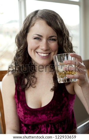 Young woman drinking a glass of Scotch.