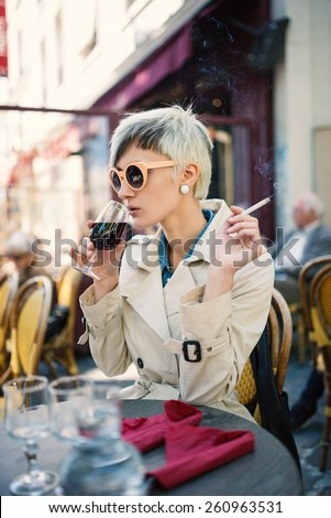 Young woman drinking a glass of wine in a cafe in Paris, France. Shallow depth of field.  - stock photo
