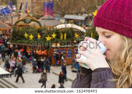 Young woman drinking a punch on christmas market