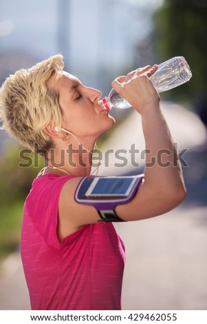 young woman drinking a water after mornig jogging workout  city  sunrise in background