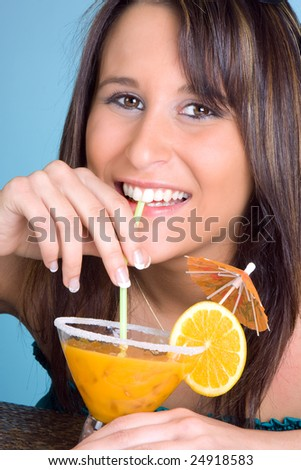 Young woman drinking an orange cocktail with a smile - stock photo