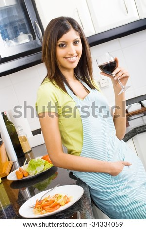 young woman drinking and eating in kitchen - stock photo