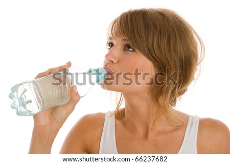 Young woman drinking bottled mineral water - stock photo