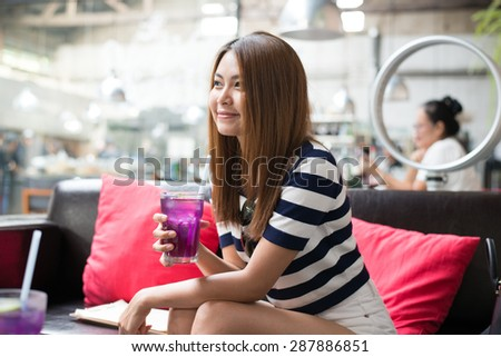Young woman drinking   Butterfly pea in a cafe